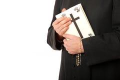 Les mains du prêtre sur la bible avec le rosaire photos libres de droits