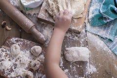 Les mains du ` s d'enfants arrachent la pâte, la farine est dispersées sur une table en bois et une serviette, une goupille et un images libres de droits