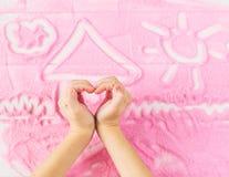 Les mains du ` s d'enfants dépeignent le coeur sur le fond du sable décoratif Images stock