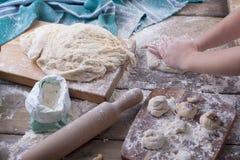 Les mains du ` s d'enfants déroulent la pâte, farine est dispersées sur une table en bois et une serviette, une goupille et un co photo stock
