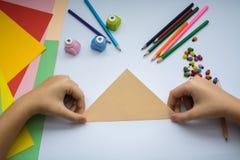 Les mains du ` s d'enfants font le loup d'origami du papier de pêche Photo stock