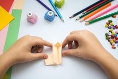 Les mains du ` s d'enfants font le loup d'origami du papier de pêche Images stock