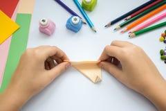 Les mains du ` s d'enfants font le loup d'origami du papier de pêche Photographie stock libre de droits