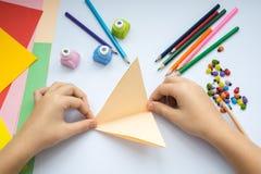 Les mains du ` s d'enfants font le loup d'origami du papier de pêche Images libres de droits