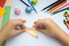 Les mains du ` s d'enfants font le loup d'origami du papier de pêche Photos stock