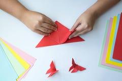 Les mains du ` s d'enfants font le papillon d'origami du papier coloré sur le fond blanc image stock