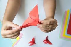 Les mains du ` s d'enfants font le papillon d'origami du papier coloré sur le fond blanc images stock