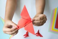 Les mains du ` s d'enfants font le papillon d'origami du papier coloré sur le fond blanc photos stock