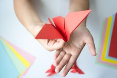 Les mains du ` s d'enfants font le papillon d'origami du papier coloré sur le fond blanc photos libres de droits
