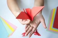 Les mains du ` s d'enfants font le papillon d'origami du papier coloré sur le fond blanc photo libre de droits