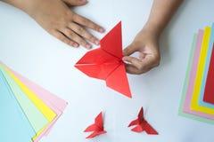 Les mains du ` s d'enfants font le papillon d'origami du papier coloré sur le fond blanc photographie stock libre de droits