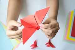 Les mains du ` s d'enfants font le papillon d'origami du papier coloré sur le fond blanc photo stock