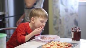 Les mains du ` s d'enfants préparent la pizza écartez le remplissage sur la pâte banque de vidéos