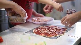 Les mains du ` s d'enfants préparent la pizza écartez le remplissage sur la pâte clips vidéos