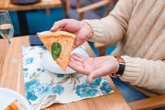 Les mains du ` s d'homme dans un chandail tiennent un morceau de pizza Plan rapproché images libres de droits