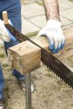 Les mains du ` s de charpentier dans les gants protecteurs indiquent avec un crayon la dimension avec un angle Images libres de droits