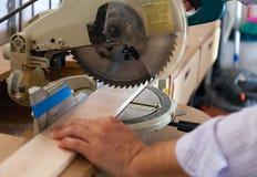 Les mains du ` s de charpentier sur le bois à la table ont vu Photos stock