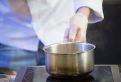 Les mains du ` s de cuisinier dans les gants blancs tiennent une casserole au-dessus d'un St électrique Photographie stock