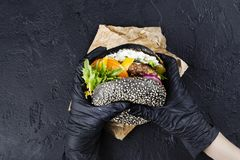 Les mains du ` s de femme dans les gants en caoutchouc noirs tiennent l'hamburger noir juteux de petit pain photographie stock libre de droits