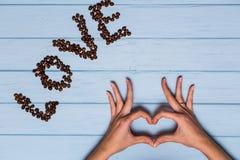 Les mains du ` s de femme dans la forme du coeur avec amour textotent des grains de café Photographie stock