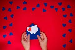 Les mains du ` s de femme tiennent l'enveloppe avec la lettre d'amour au-dessus du fond rouge Image libre de droits