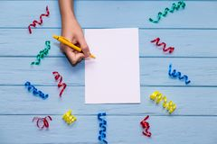Les mains du ` s de femme tiennent le stylo et l'écriture sur le papier blanc blanc avec les rubans colorés autour Images stock