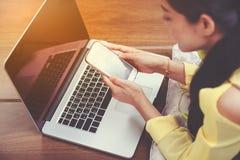 Les mains du ` s de femme utilisant le téléphone et l'ordinateur portable intelligents sur le plancher courtisent image stock