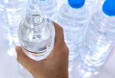 Les mains du ` s de femmes ont pris les bouteilles d'eau en plastique qui sont ouverts photographie stock libre de droits