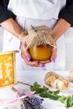 Les mains du ` s de femmes tiennent un pot de miel Photographie stock