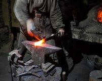 Les mains du ` s de forgeron avec le marteau du ` s de forgeron sont passionnées à fonte Image stock