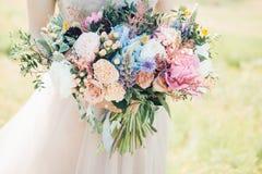 Les mains du ` s de jeune mariée tiennent le beau bouquet nuptiale de la pivoine Photographie de beaux-arts photographie stock