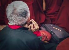 Les mains du ` s de moine bouddhiste de vieil homme dans la prière font des gestes Photos stock