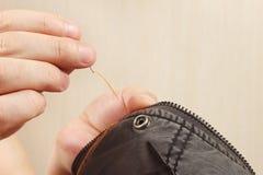 Les mains du snipper cousent les vêtements noirs de coton avec la fin d'aiguille  Image libre de droits