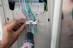 Les mains du technicien utilise un moteur électrique pour serrer l'écrou photos stock