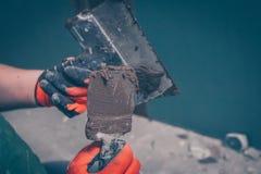 Les mains du travailleur dans les gants tiennent des spatules avec la colle de tuile photographie stock libre de droits