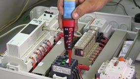 Les mains du travailleur vérifient l'indicateur de tension de contacts dans l'électronique dans l'usine banque de vidéos