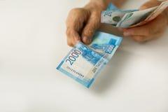 Les mains du vieil homme tiennent de grandes factures russes de la dénomination de 1,2,5 mille images libres de droits