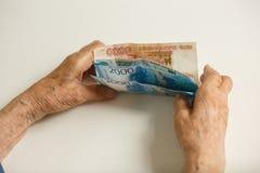 Les mains du vieil homme tiennent plusieurs grandes dénominations photo stock
