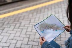 Les mains du voyageur tenant la carte à la plate-forme de station de train, avec l'espace de copie Photographie stock libre de droits