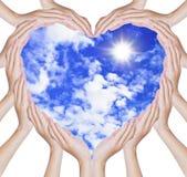 Les mains effectuent la forme de coeur sur le ciel bleu Photographie stock libre de droits