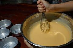Les mains eggs l'oeuf de mélange de beurre et de sucre dans la cuvette images libres de droits