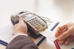 Les mains emploient la machine EDC de saisie de données électroniques ou la carte de crédit photos libres de droits