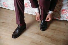 Les mains en gros plan d'un homme attachent des dentelles sur les chaussures noires Un homme d'affaires dans des pantalons et des Photographie stock libre de droits