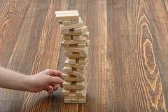 Les mains en gros plan de l'homme retire les briques en bois Images libres de droits