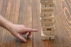 Les mains en gros plan de l'homme retire les briques en bois Photos libres de droits