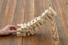 Les mains en gros plan de l'homme retire les briques en bois Photos stock