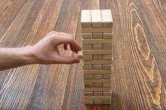 Les mains en gros plan de l'homme retire les briques en bois Image libre de droits