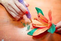 Les mains en gros plan de la femme, décorant la fleur artificielle de lis avec des fausses pierres brillantes colorées photographie stock