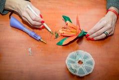 Les mains en gros plan de la femme, décorant la fleur artificielle de lis avec des fausses pierres brillantes colorées image libre de droits