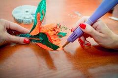 Les mains en gros plan de la femme, décorant la fleur artificielle de lis avec des fausses pierres brillantes colorées photos libres de droits